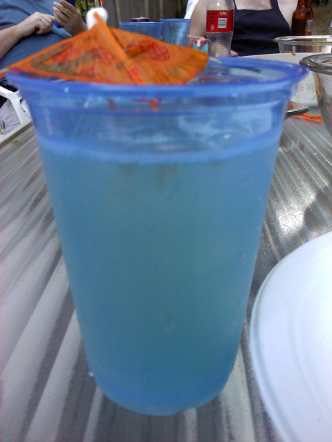 A blue plastic cup filled with a Lillet spritzer. An orange paper umbrella is hanging over the rim.