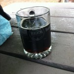 A Toronto's Festival of Beer glass mug partly filled with Krombacher Dark on a wooden picnic table.