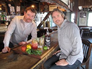 Mike McQuade and Jason Laan sit at a bar with a bottle of Old Whalers Style Sag Harbor Hand Crafted Rum